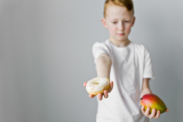 Portrait of a confused kid boy choosing between donut and mango over grey background