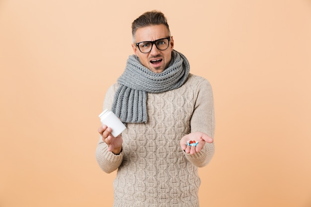 Portrait of a confused man dressed in sweater and scarf standing isolated over beige wall, showing pills capsules
