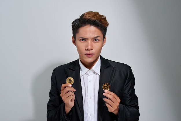 Portrait of a confused mature businessman dressed in suit holding two golden bitcoins isolated over gray background