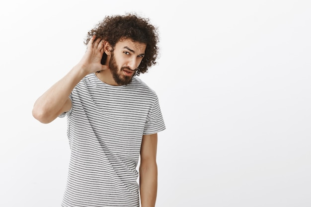 Ritratto di studente maschio attraente confuso misheard in maglietta a strisce, tenendo il palmo vicino all'orecchio per sentire meglio, guardando da sotto la fronte