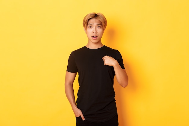 Portrait of confused and sad asian blond guy, frowning upset and pointing at himself, standing yellow wall