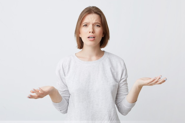 Portrait of confused upset young woman in longsleeve looks puzzled