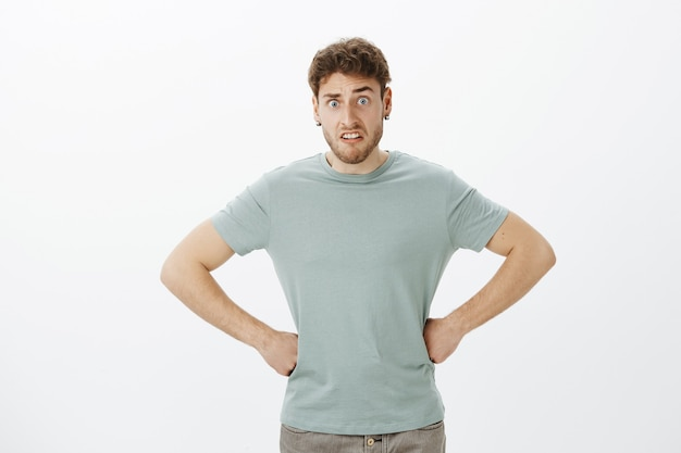 Ritratto di strano modello maschio caucasico confuso con setole, tenendo le mani sui fianchi, sollevando gli occhi e fissando interrogato, essendo scioccato dal pasticcio dopo la festa dei bambini