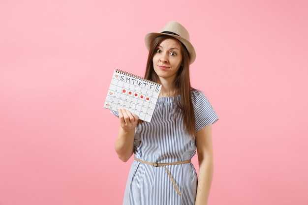 Portrait of confused woman in blue dress, hat holding periods calendar for checking menstruation days isolated on bright trending pink background. medical healthcare, gynecological concept. copy space