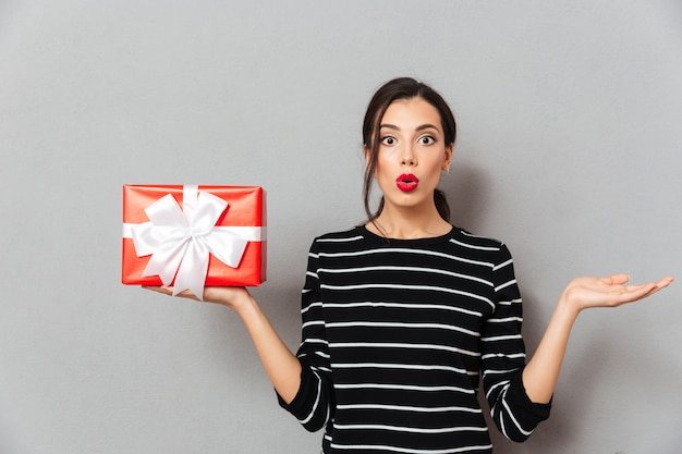 Portrait of a confused woman holding gift box