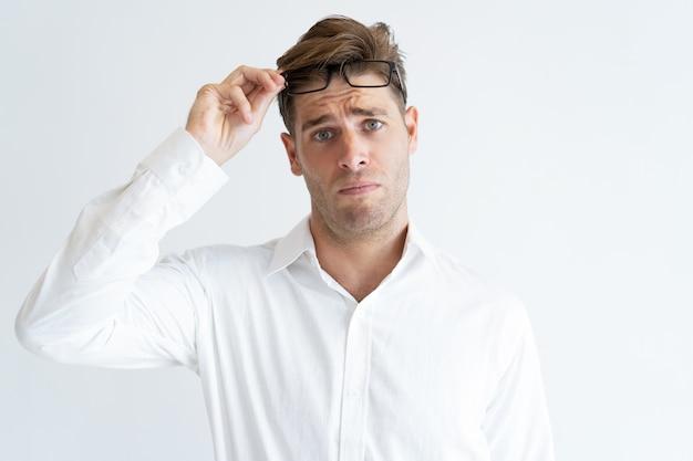 Portrait of confused young businessman raising eyeglasses