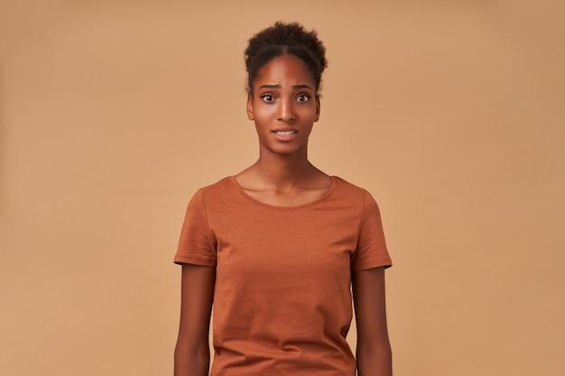 Ritratto di giovane donna riccia dai capelli scura e confusa che aggrotta le sopracciglia mentre guarda perplesso, in piedi sul beige con le mani verso il basso