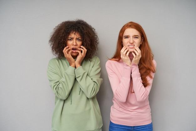 Ritratto di giovani amiche graziose confuse che aggrottano le sopracciglia e tengono le mani alzate sulle guance mentre guardano con il broncio, in piedi contro il muro grigio