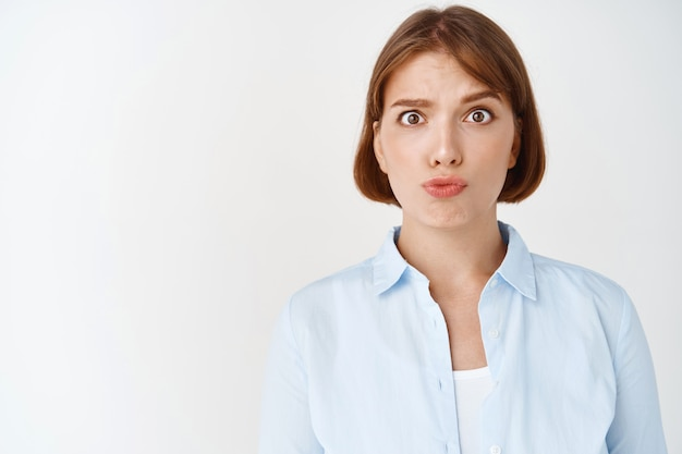 Portrait of confused young woman raising eyebrows and pucker lips puzzled, cant understand, standing in stupor on white wall. girl grimacing clueless