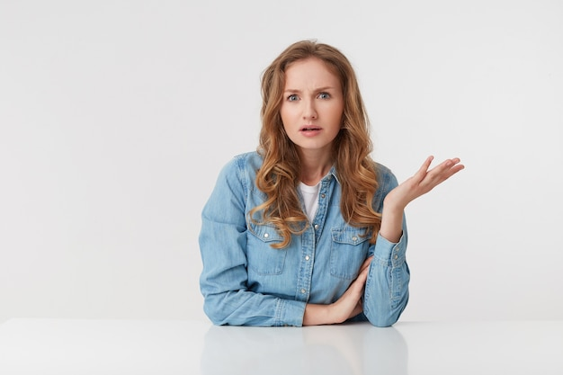 Portrait of confused young woman with long blond wavy hair, sitting at the table, one palm raised, looks skeptically displeased indignantly with incomprehension, over white background.
