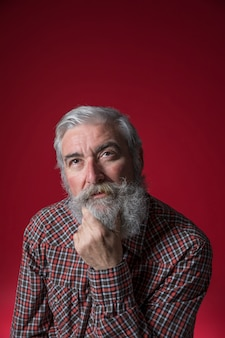 Portrait of contemplated senior man with hand on his chin looking up against red background