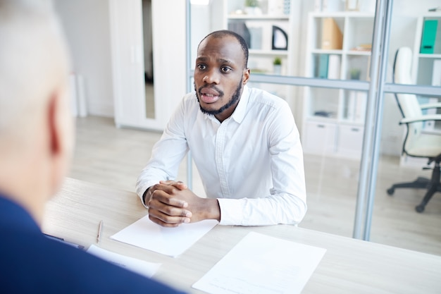 Portrait of contemporary african-american man answering questions to hr manager during job interview in office, copy space