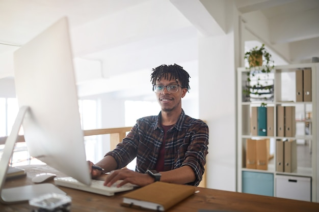 Portrait of contemporary african-american man smiling at camera while using computer and typing on keyboard in white office, it developer concept, copy space