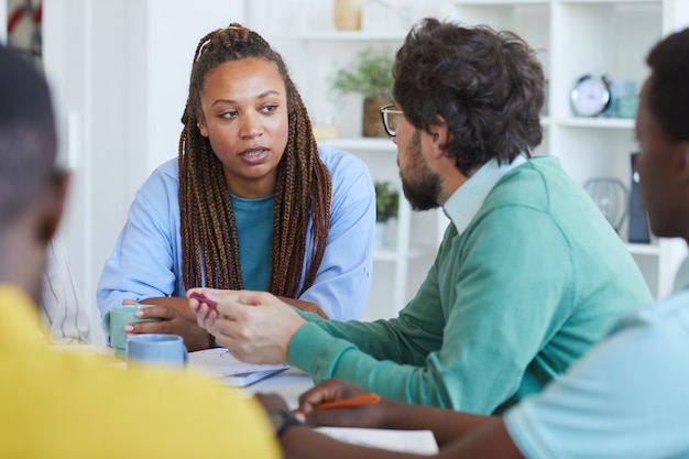 Portrait of contemporary african-american woman talking to colleagues during business meeting in office