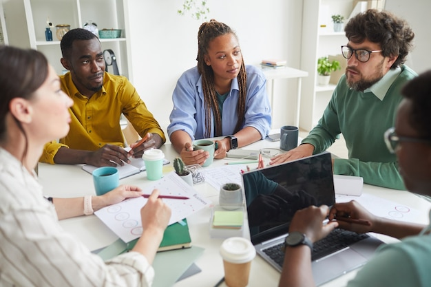 Portrait of contemporary multi-ethnic team discussing business project while sitting at cluttered table in conference room and listening to manager