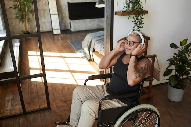 Portrait of contemporary tattooed woman with disability listening to music while relaxing at home, copy space