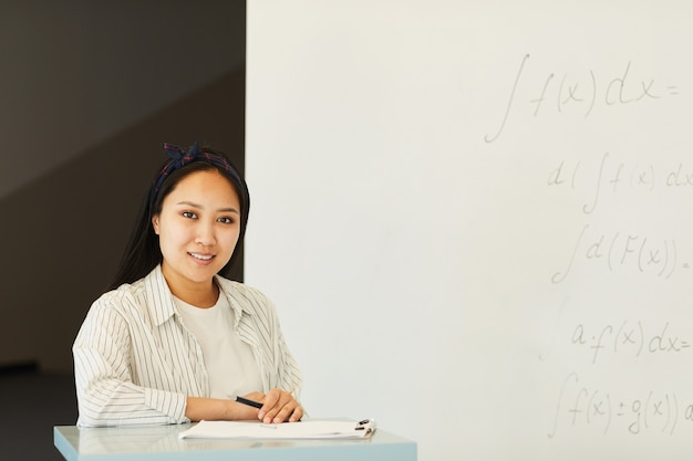Portrait of content attractive asian student girl standing at lecture stand with papers against whiteboard in classroom