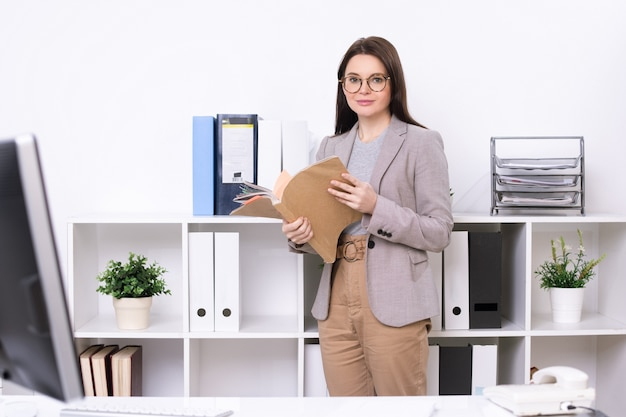 Portrait of content stylish secretary in eyeglasses standing at office shelves and finding file in folder