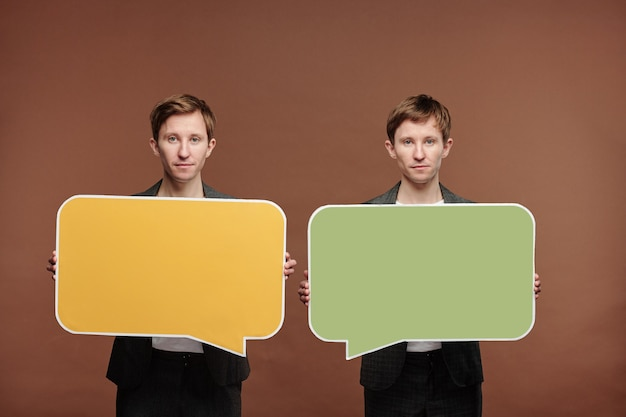 Portrait of content twin brothers standing against brown background and holding colorful speech bubble tags