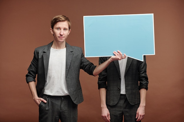 Portrait of content young man in smart casual suit hiding face of man behind speech bubble tag against brown background