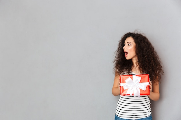 Portrait of contented and candid female with curly dark hair holding red box gift wrapped being excited and surprised copy space