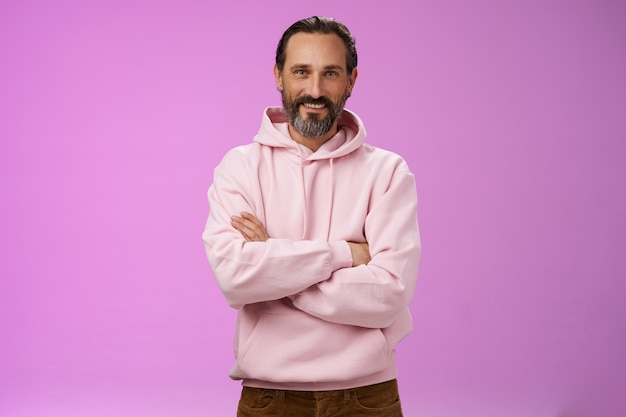 Portrait cool bearded mature grandad trying stay stylish urban trends wear pink hoodie cross arms chest casual pose smiling happily talking have conversation, posing purple background.