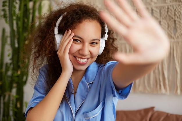Ritratto di una bella signora dalla pelle scura con i capelli ricci, che ascolta la musica preferita in cuffia e prova il viso coperto dalla fotocamera con la mano, sorride ampiamente e tocca la guancia.