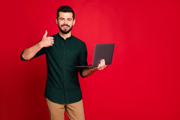 Portrait of cool positive cheerful guy laptop user online shopping customer search discounts recommend show thumb up sign wear stylish brown pants trousers