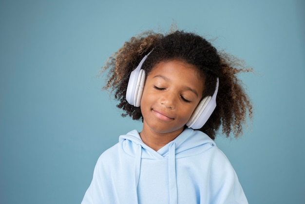 Portrait of cool teenage boy listening to music on headphones