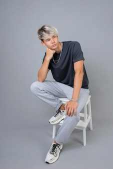 Portrait of cool teenage boy posing on a chair