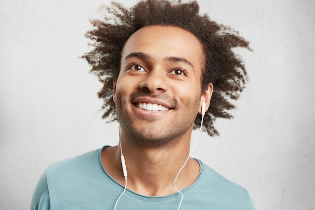 Portrait of cool young black man with curly hair, has cheerful expression