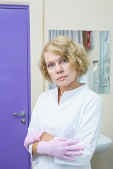 Portrait of cosmetologist posing in pink latex gloves in cosmetology cabinet. beauty facial treatment. lifting effect.
