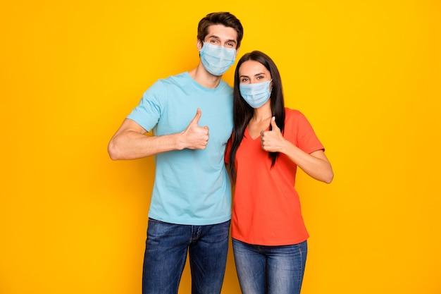 Portrait of couple guy lady embracing showing thumbup wearing gauze safety mask