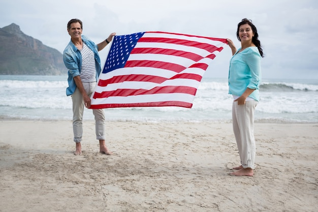 Portrait of couple holding american flag on beach