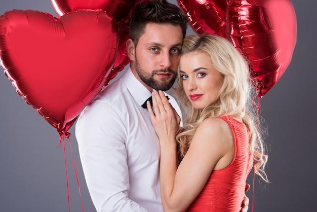 Portrait of couple holding heartshape balloons