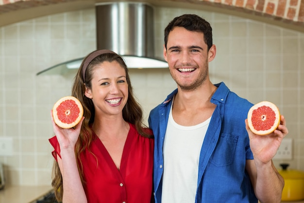Portrait of couple holding slices of blood orange in kitchen
