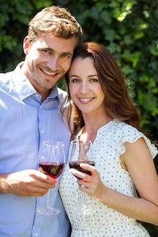 Portrait of couple holding wineglasses at front yard