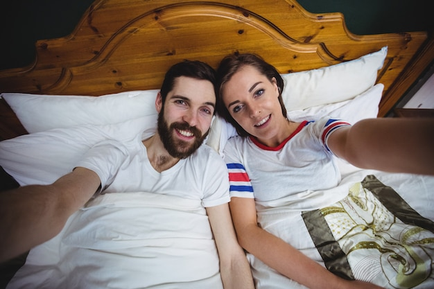 Portrait of couple lying together on bed