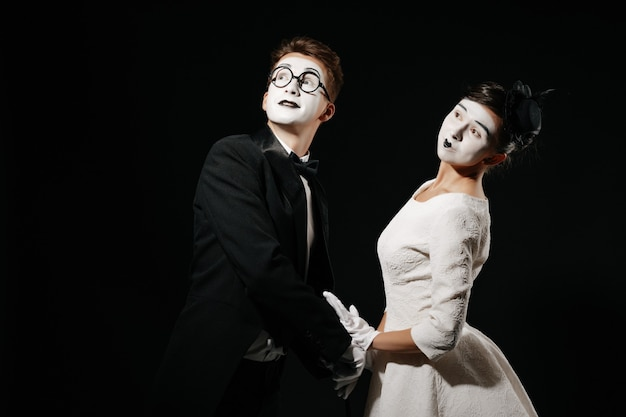 Portrait of couple mime on black background. man in tuxedo and glasses and woman in white dress