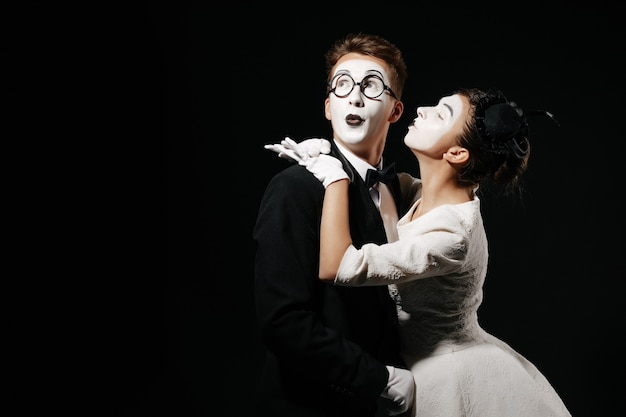 Portrait of couple mime on black background. woman in white dress kissing man in tuxedo and glasses
