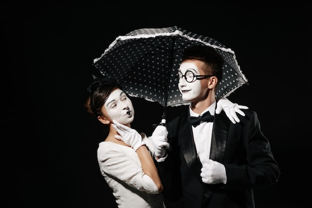 Portrait of couple mime with umbrella on black background. man in tuxedo and glasses and woman in white dress