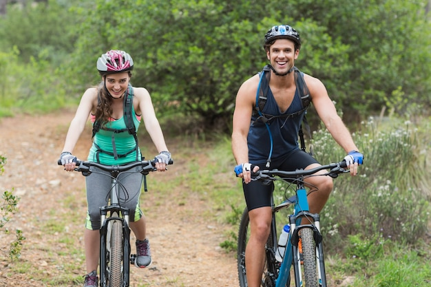 Portrait of couple riding bicycles on dirt road
