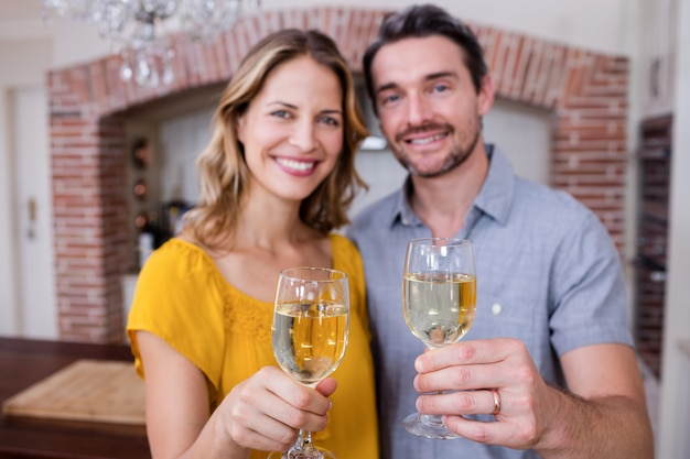 Portrait of a couple showing a glass of wine