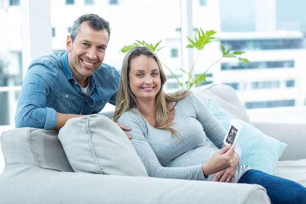 Portrait of couple sitting on sofa and holding ultrasound scan