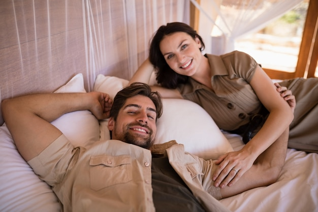 Portrait of couple smiling while lying on canopy bed