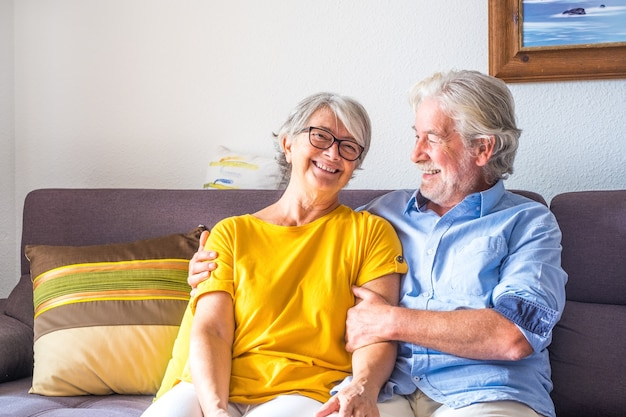 Portrait of couple of two happy and healthy seniors old people smiling and looking at the camera. close up of mature grandparents enjoying and having fun together at home indoor.
