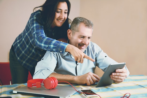Portrait of couple using laptop at home