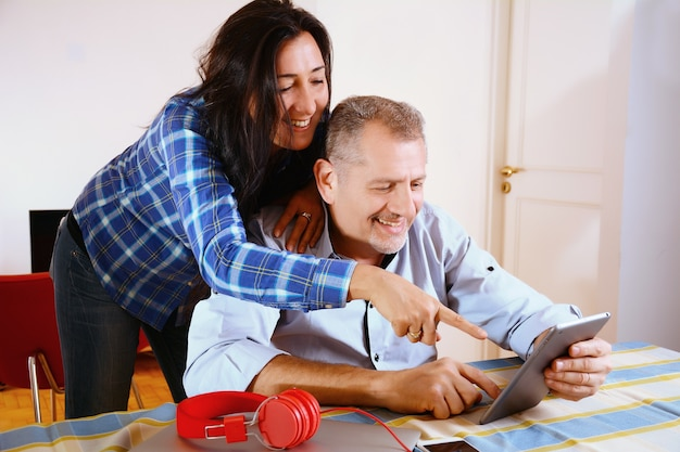 Portrait of couple using ltablet at home