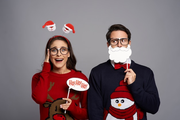 Portrait of couple with funny photo booth gadgets