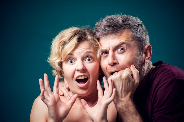 A portrait of couple with scared and shocked faces. people and emotions concept